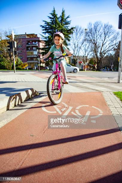 little girl riding her bicycle in the city - bicycle lane stock pictures, royalty-free photos & images
