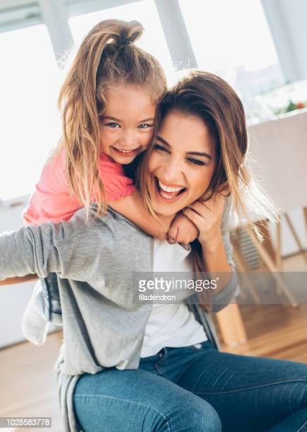 little girl riding her mоther on piggyback - cavalitas imagens e fotografias de stock