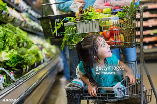 Little girl riding in bottom basket of supermarket shopping cart