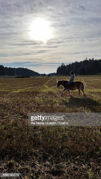 Little Girl Riding Pony In Field