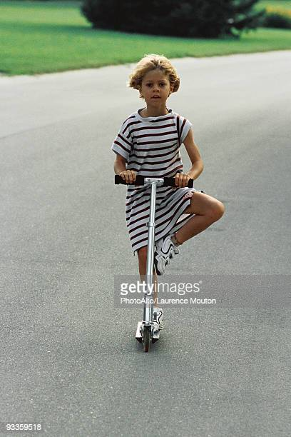 Little girl riding push scooter