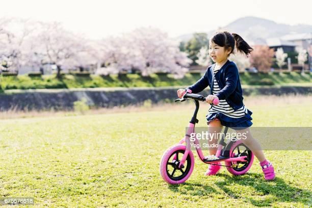 Kleines Mädchen reiten Laufrad in Natur.