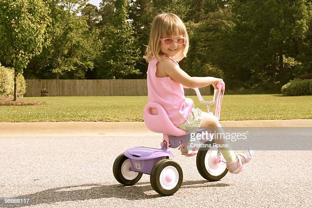little girl riding tricycle on street - tricycle stock pictures, royalty-free photos & images