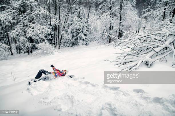 Little girl rolling down in beautiful winter forest