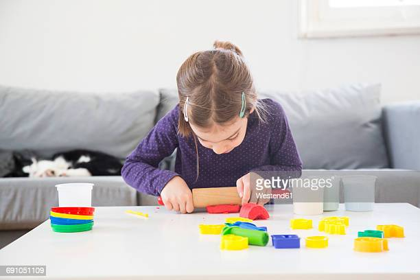 Little girl rolling out modeling clay