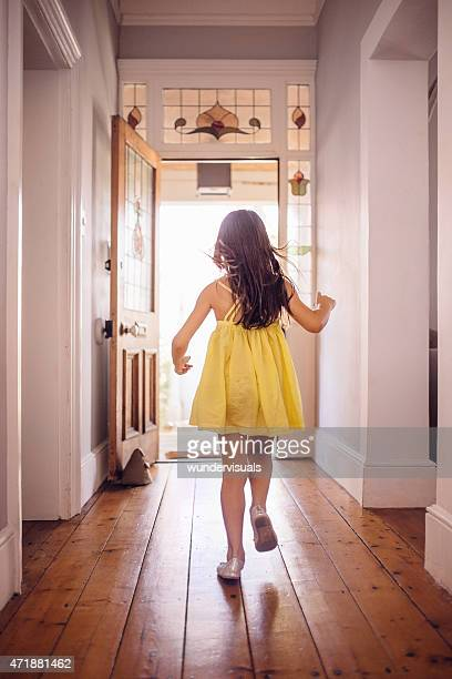 little girl running happily to an open front door - yellow dress stock pictures, royalty-free photos & images