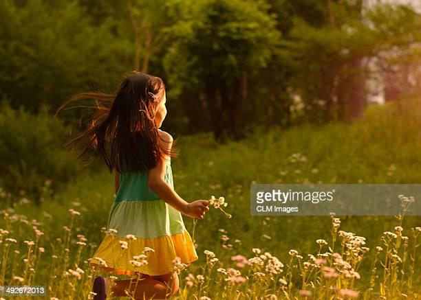 Little girl running in a field of flowers
