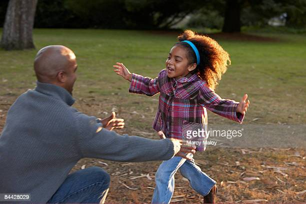 Little girl running into her father's arms.