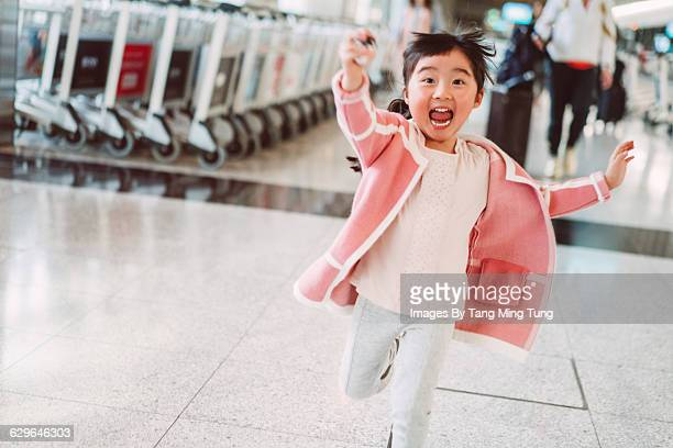 little girl running joyfully in airport - kid in airport stock pictures, royalty-free photos & images