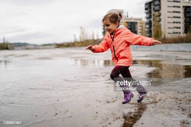 little girl running on a ground wet from rain on cloudy day - silver boot stock pictures, royalty-free photos & images