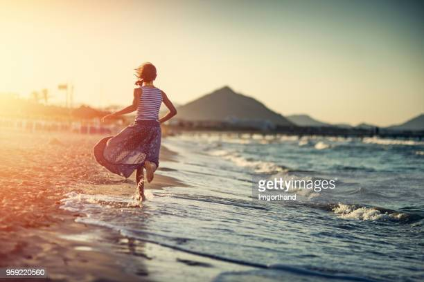 little girl running on beach on sunset - sundress stock pictures, royalty-free photos & images