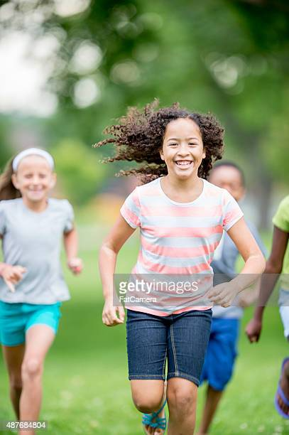 little girl running outside - kids playing tag stock photos and pictures