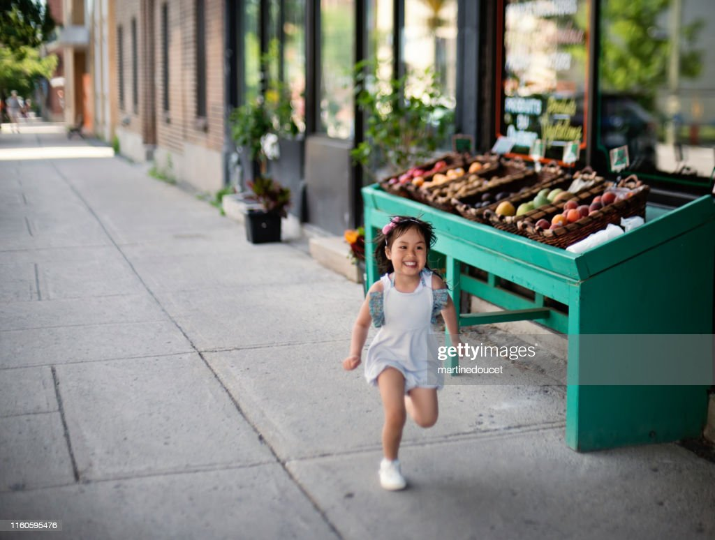 Little girl running outside zero waste oriented fruit and grocery store. : Stock Photo