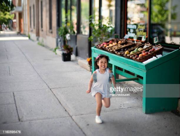 """little girl running outside zero waste oriented fruit and grocery store. - """"martine doucet"""" or martinedoucet stock pictures, royalty-free photos & images"""