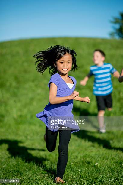 little girl running - kids playing tag stock photos and pictures