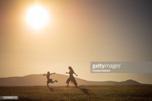 Little girl running through the rural sunset pastures of Keswick, England
