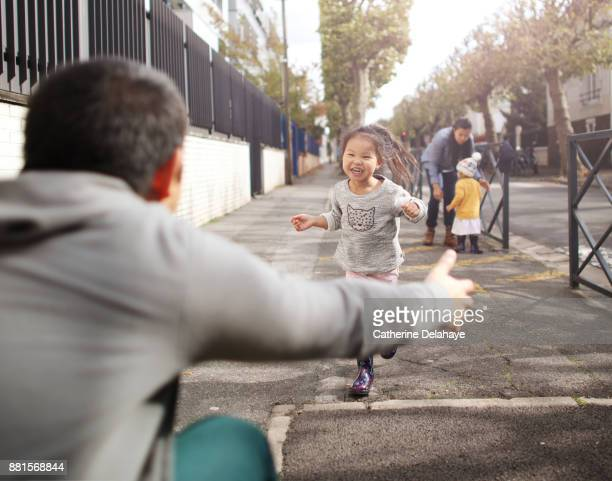 A little girl running to the arms of her dad in the street