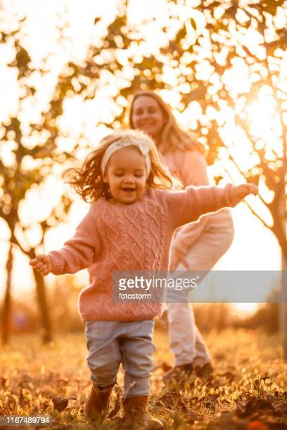 Little girl running while playing with her mother at the park