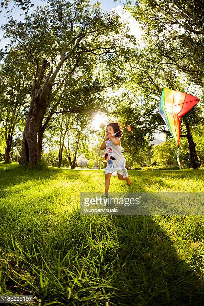 Little Girl Running With a Kite In Garden