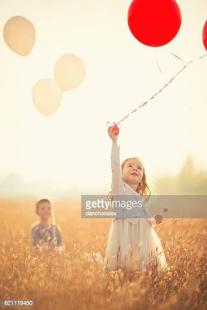 Kleines Mädchen läuft mit Ballons