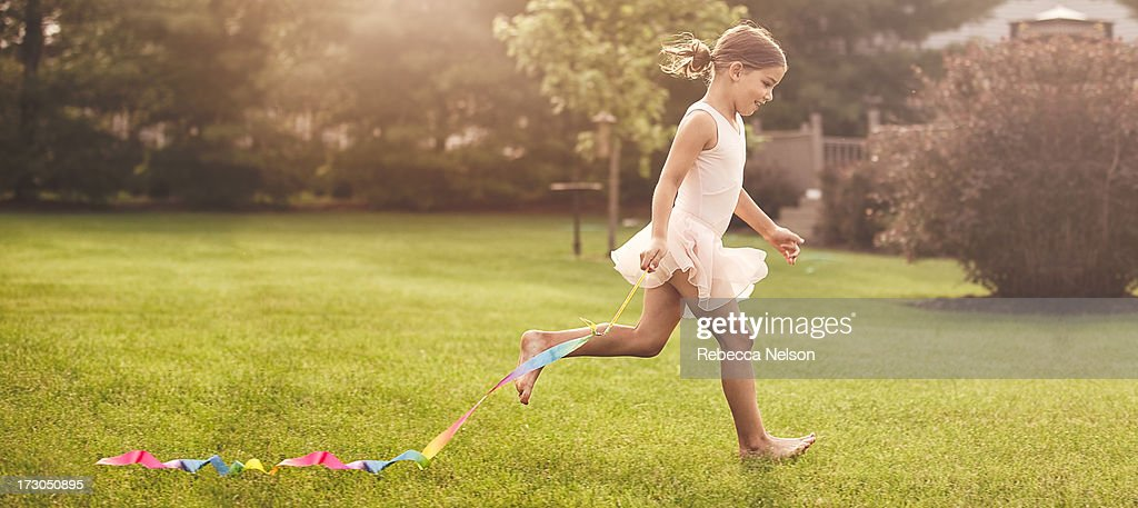 little girl running with gymnastics ribbon : Stock Photo