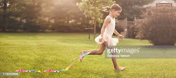 little girl running with gymnastics ribbon