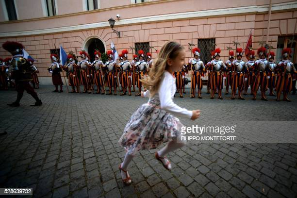 A little girl runs infront of the new swiss guard prior to a swearingin ceremony in Vatican City on May 6 2016 The annual swearing in ceremony for...