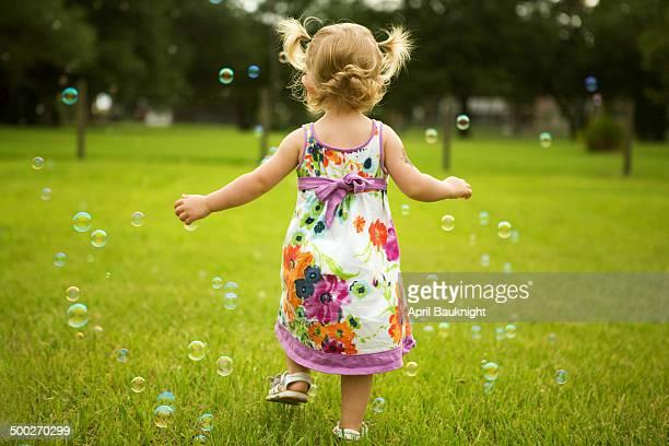little girl runs through bubbles