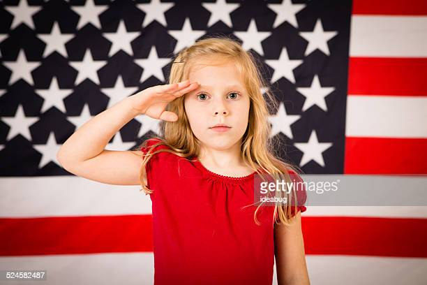 Little Girl Saluting in Front of American Flag