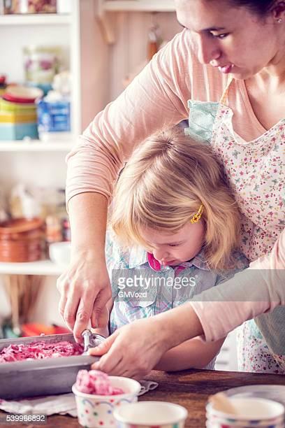 Kleines Mädchen ausschöpfen hausgemachte Erdbeer Eiscreme mit ihrer Mutter