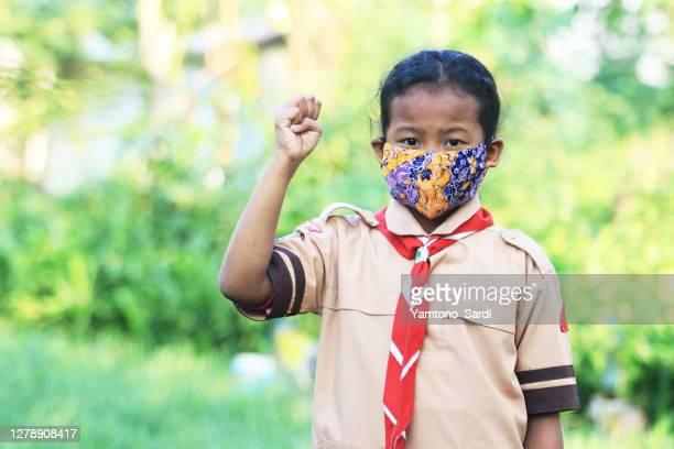 マスクを着用した小さなガールスカウト - indonesia logistics ストックフォトと画像