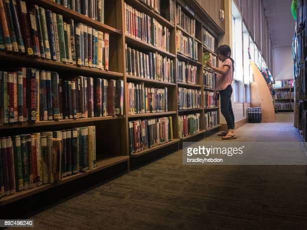 Little girl searching for a book in library