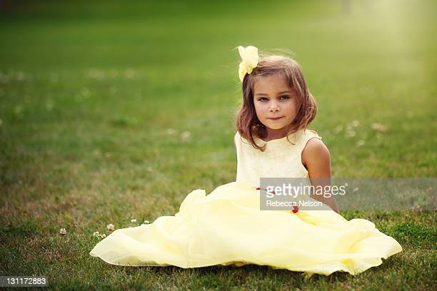 Little girl seated on grass in fancy yellow dress