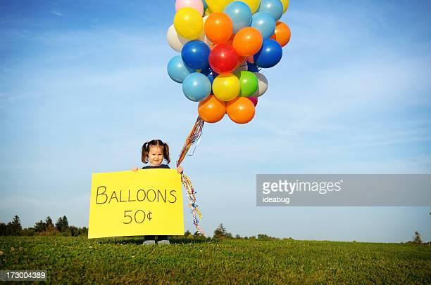 Kleines Mädchen mit Luftballons im Verkauf