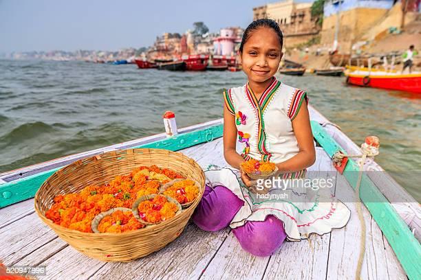 Little girl selling flower candles in boat, Ganges River, Varanasi