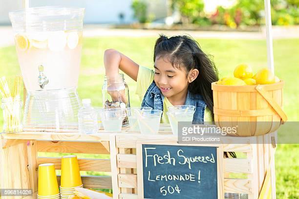 Little girl sells lemonade in her front yard