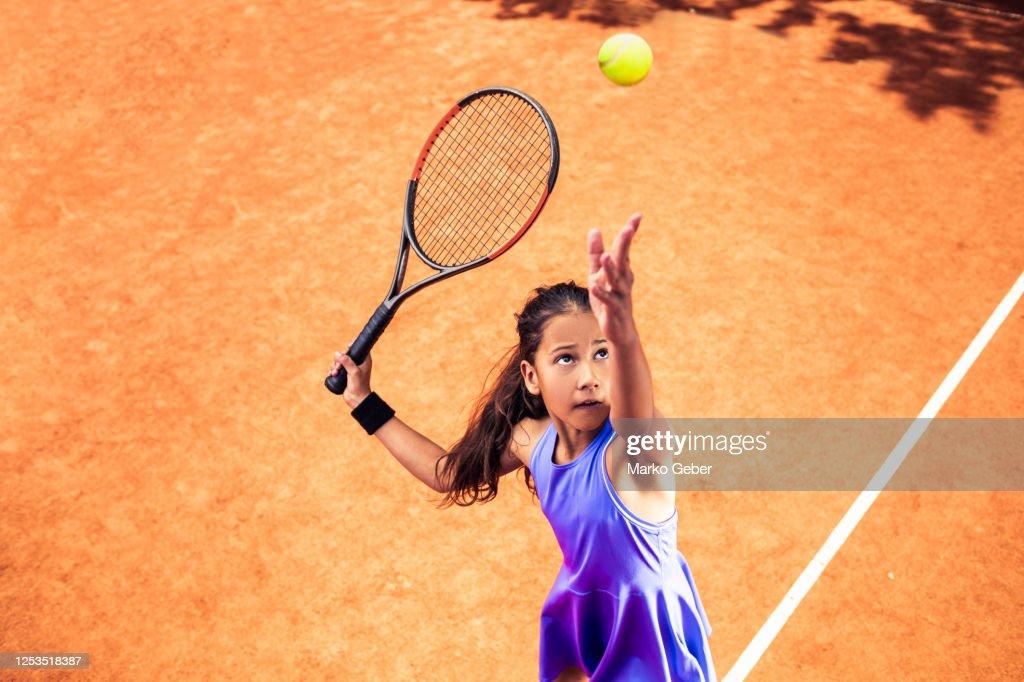 Little Girl Serving in Tennis : Stock Photo