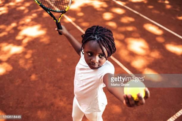little girl serving in tennis - ジュニアレベル ストックフォトと画像