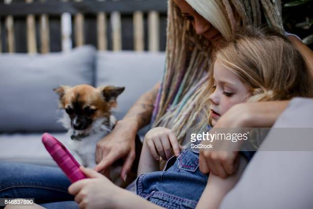 Little Girl Sharing a Digital Tablet with Her Hipster Mother