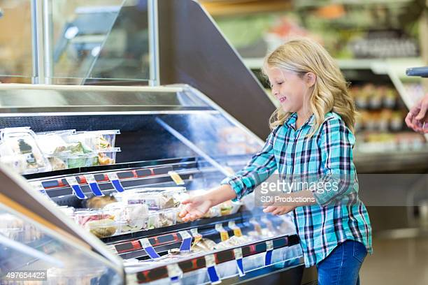 Little girl shopping at deli counter with mom in supermarket