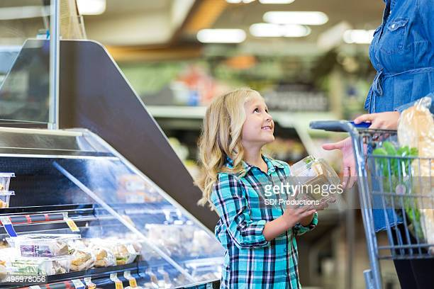 Little girl shopping at deli in grocery store with mom