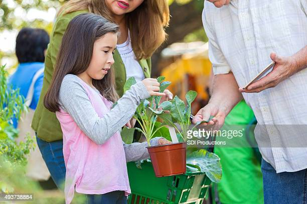 Little girl shopping for plants with mother at gardening store