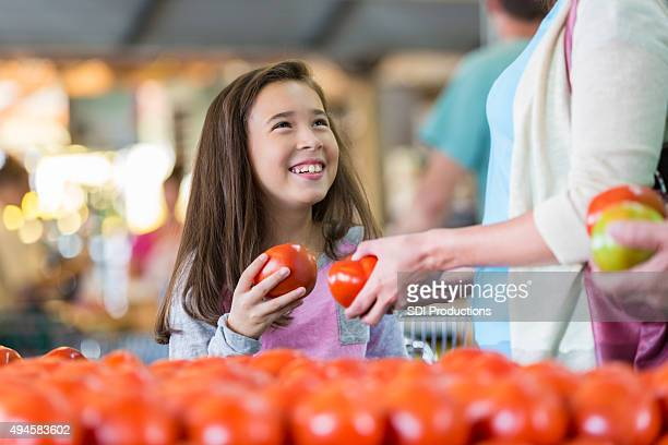 Little girl shopping for produce at market with mother