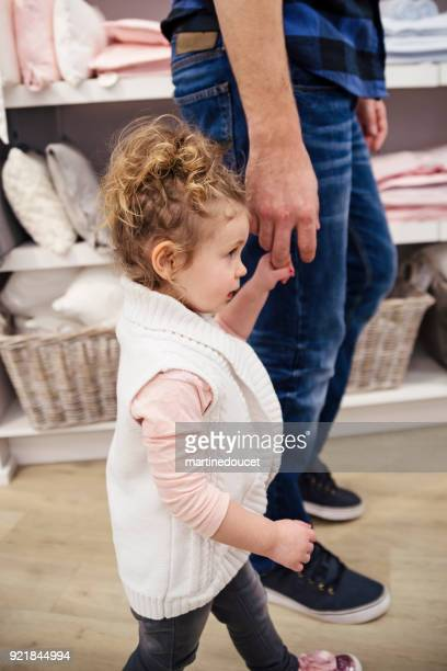 Little girl shopping with father in children store.