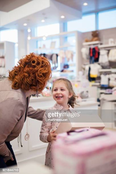 Little girl shopping with mother in children store.