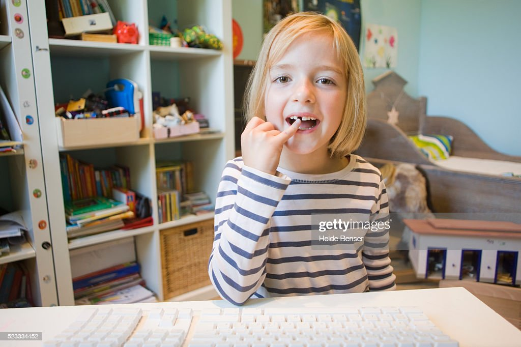 Little girl showing a lost tooth on an Internet video phone call : Foto de stock