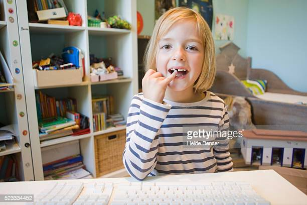 little girl showing a lost tooth on an internet video phone call - webcam photo ストックフォトと画像