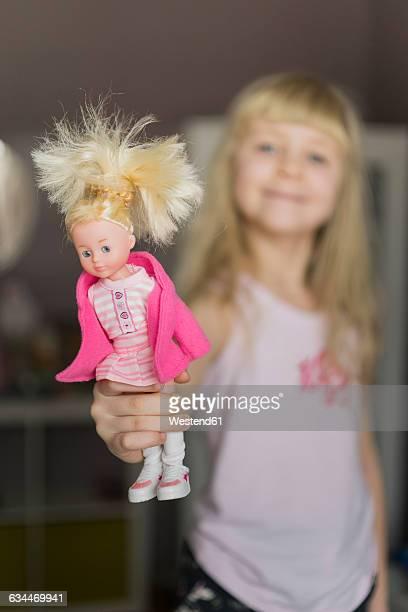 Little girl showing doll
