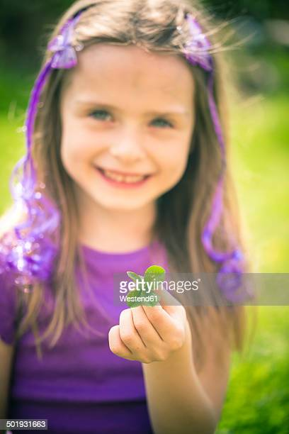 Little girl showing four leaved clover