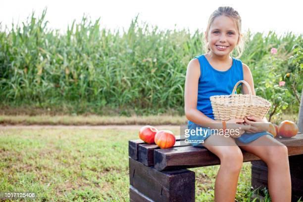 Little girl showing fresh harvested tomato